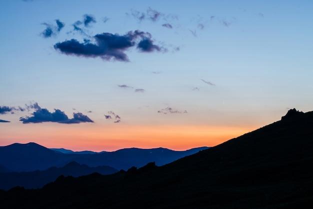 Теплый градиент рассветного неба над слоями силуэтов гор и скал.