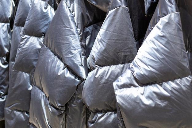 Теплые серые серебряные куртки висят на вешалках в магазине, тканевый фон