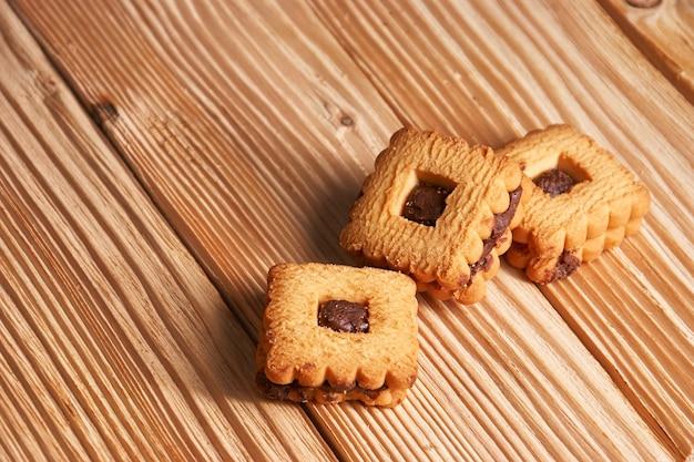나무 테이블에 초콜릿을 얹은 따뜻한 홈 메이드 진저 스냅 쿠키