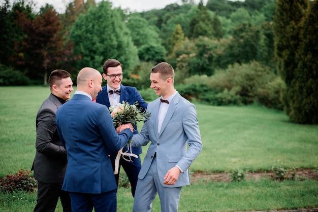 Warm hugs of groom and groomsmen in green park