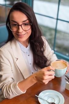 Warm inside. top view of satisfied elegant ogres woman sitting at the table while wearing glasses and enjoying coffee