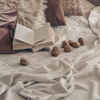 くるみと開いた本のあるリビングルームの暖かいインテリア。読んで、休憩。冬の週末のコンセプトです。居心地の良い秋や冬のコンセプトです。