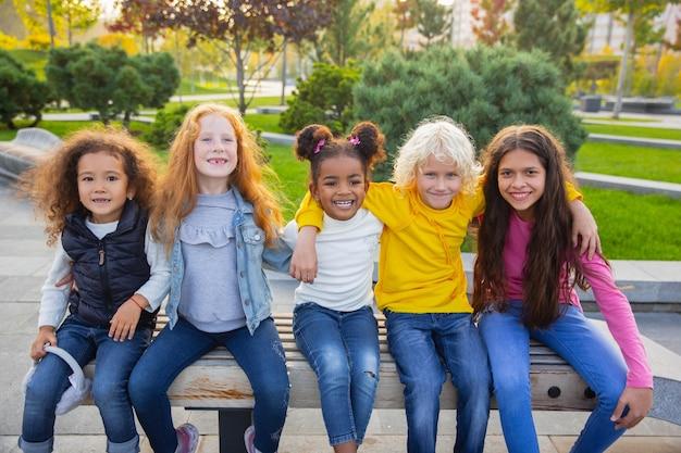 暖かい。夏の日に公園で一緒に遊ぶ子供、女の子、男の子の異人種間のグループ。