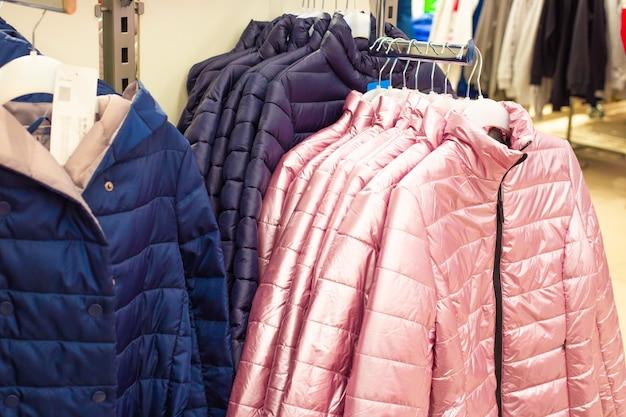 Теплые куртки светло-серебристо-розового цвета вешают на вешалку в магазине, демисезонная одежда.