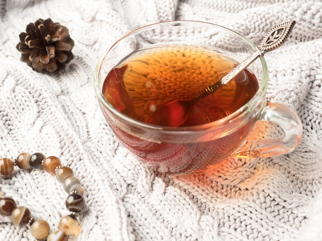 Warm knit sweater, a cup of hot tea with chocolate and winter decorations,