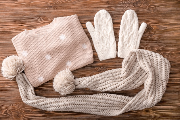 Warm knitted clothes on wooden surface. seasonal female wardrobe