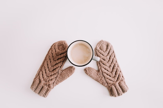 Теплые вязаные варежки с чашкой кофе, изолированные на белом фоне