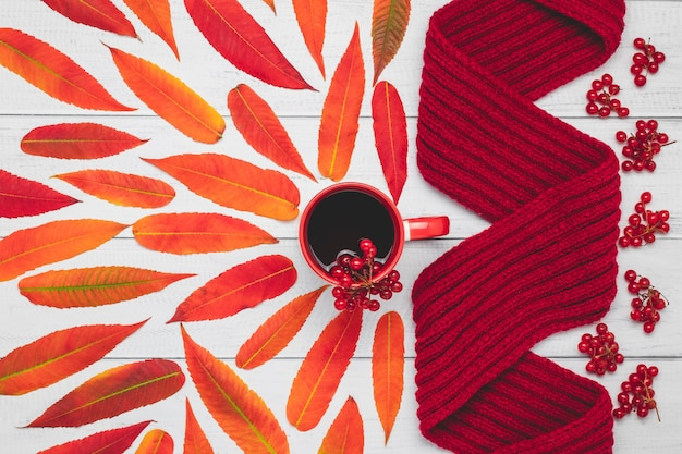 木の板に赤い葉が付いた暖かいニットのスカーフとティーマグ、秋の構成。