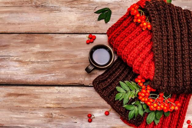 Warm knitted scarf, hot drink, ripe rowan berries