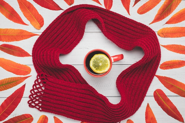 Warm knitted scarf and a red cup of tea with orange leaves on a wood table, autumn composition.