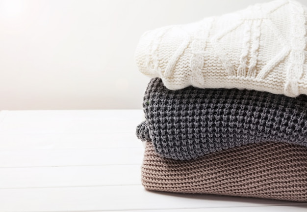 Warm knitted winter sweaters in stack