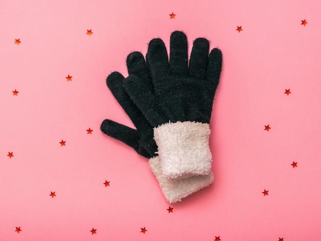 Теплые вязаные женские перчатки на розовом фоне с блестками. женские аксессуары для холода.