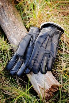 따뜻한 가죽 남성용 장갑이 잔디 위에 놓여 있습니다.
