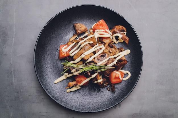 鶏レバー、キノコのフライ、オリーブオイル、調味料、バルサミコ酢の温かいレタスサラダ。美味しいグルメディナー。セレクティブフォーカス。