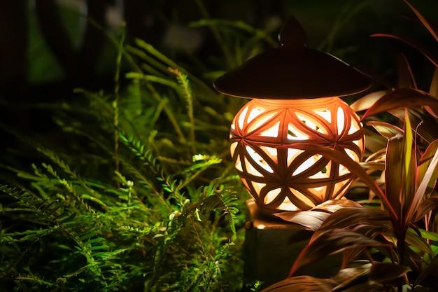 緑豊かな公園にある街灯からの暖かい光。夜、外の芝生で光ります。閉じる。コテージとファゼンダのデザインと装飾