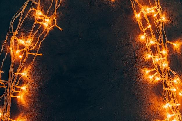 따뜻한 빛 조명 화환은 어두운 배경에 닫습니다