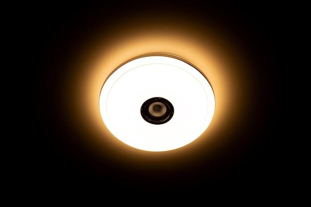 검정색 배경 위에 무선 스피커가 내장된 따뜻한 조명 led 천장 조명.
