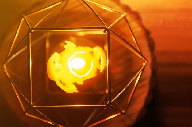 木製スライスのキャンドルホルダーにある手作りの天然蜂ワックス染めキャンドルの温かい光