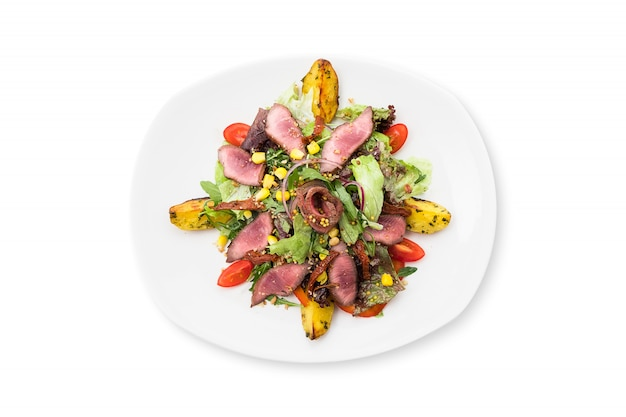Warm meat salad with arugula, mix salad, dried tomato, pine nut, beef and potatoes on a white plate isolated.
