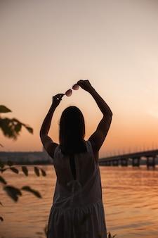 Теплые воспоминания о лете момент радости для женщины на закате на природе у реки с силуэтом ...