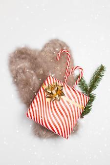 선물 상자, 깜짝 선물, 사탕 지팡이 및 상록 스프루스 가지가있는 따뜻한 장갑
