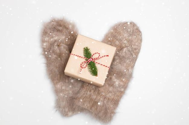 가문비 나무 가지가있는 공예 종이로 싸인 선물 상자가있는 따뜻한 장갑