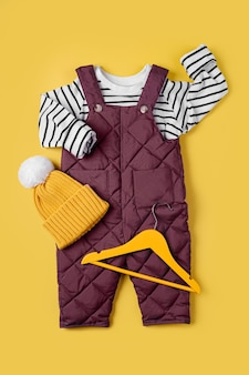 노란색 배경에 모자가 달린 따뜻한 바지와 줄무늬 점퍼. 겨울용 아기 옷 세트입니다. 패션 아동복.