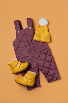 오렌지 배경에 따뜻한 바지 모자와 부츠. 겨울용 아기 옷 세트입니다. 패션 키즈 복장.