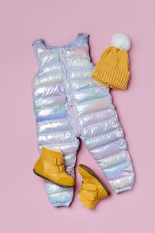 분홍색 배경에 따뜻한 바지 모자와 부츠. 겨울용 아기 옷 세트입니다. 패션 아동복.