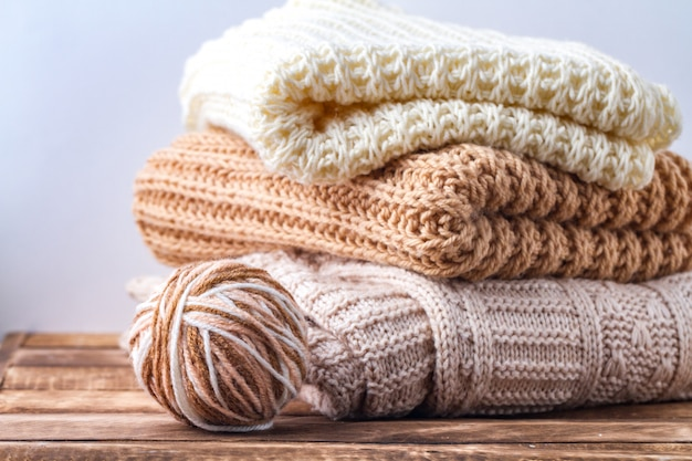 Warm, pastel clothes, knitted, pastel-colored scarves and a ball of knitting yarn winter, autumn clothes.