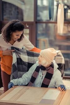 따뜻한 격자 무늬. 따뜻한 체크 무늬를 제공하면서 손님을 돌보는 좋은 친절한 여성