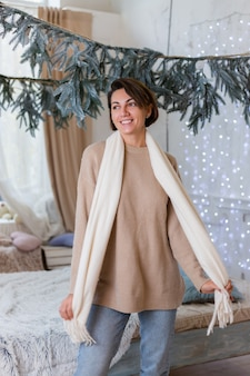 Warm portrait of happy woman in sweater, jeans and white scarf at home in bedroom