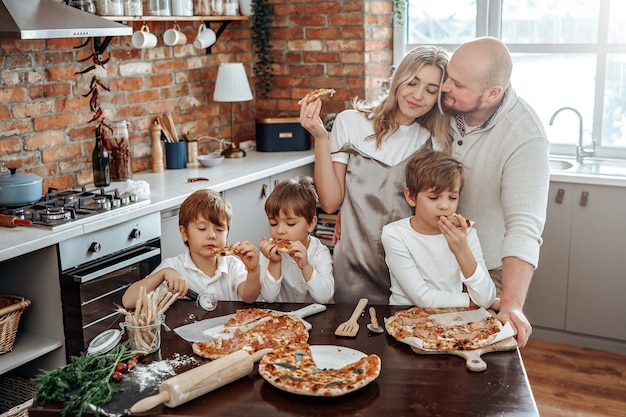 Warm portrait of a happy and young family they taste a domestic pizza. loving couple and their children in the kitchen.