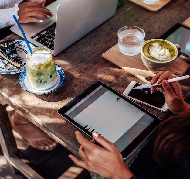 彼女はコーヒーと水カップを持ってテーブルに座って、晴れた日に外でタブレットで作業しているアジアの女性の暖かい肖像画。