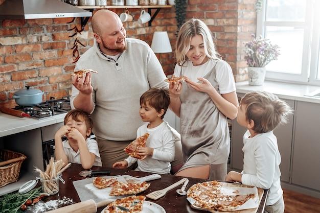 Теплый портрет счастливой и молодой семьи они пробуют домашнюю пиццу. влюбленная пара и их дети на кухне.