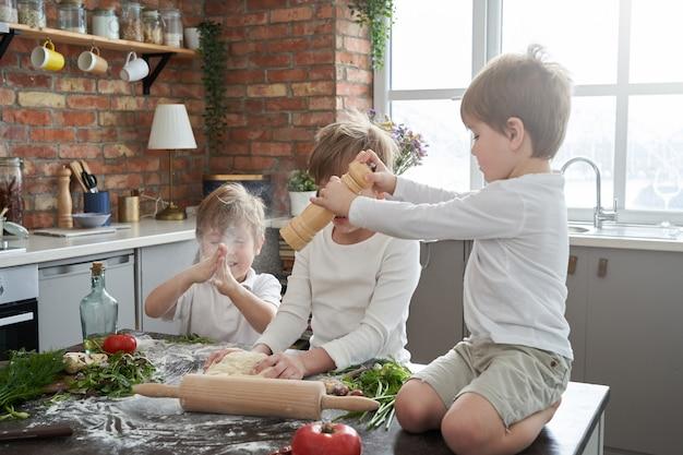 형제의 좋은 관계의 따뜻한 초상화. 세 명의 미취학 아동이 현대식 주방에서 즐거운 시간을 보내고 요리를 배웁니다.