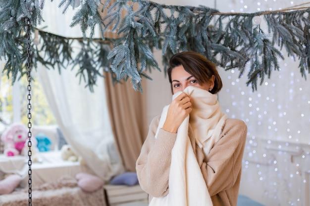 Теплый портрет счастливой женщины в свитере, джинсах и белом шарфе дома в спальне