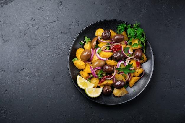Теплый картофельный салат с оливками, перцем, петрушкой и красным луком на черной керамической тарелке на темной бетонной поверхности