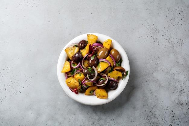 Теплый картофельный салат с оливками, перцем, петрушкой и красным луком на старой белой керамической тарелке на серой бетонной поверхности