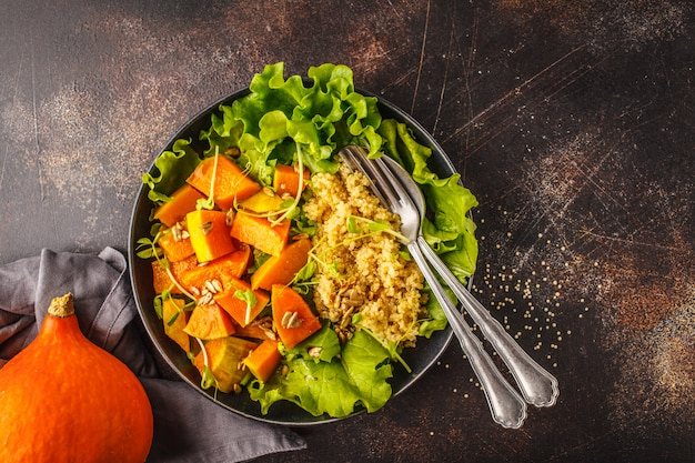 Warm quinoa and pumpkin salad in a white plate on dark background, top view.