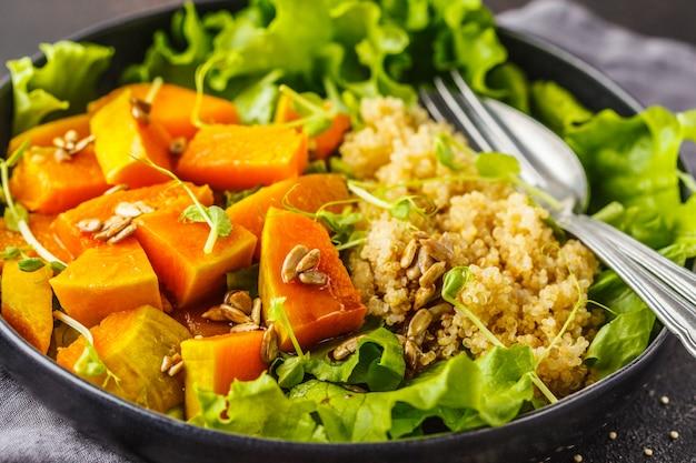 Warm quinoa and pumpkin salad in a white plate on dark background.