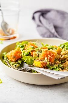 Warm quinoa and pumpkin salad in a white plate.