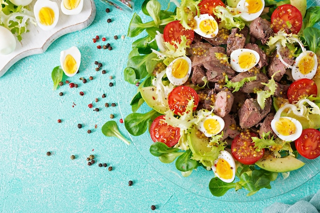 Warm salad from chicken liver, avocado, tomato and quail eggs. healthy dinner. dietary menu. flat lay. top view