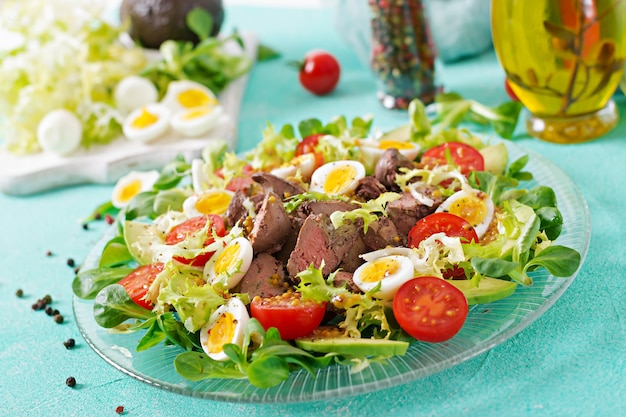 Warm salad from chicken liver, avocado, tomato and quail eggs. healthy dinner. dietary menu.
