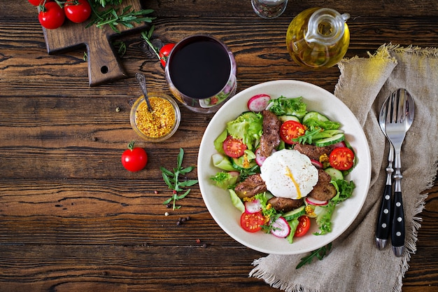 Warm salad from chicken liver, radish, cucumber, tomato and egg poached. healthy food.. top view. flat lay.
