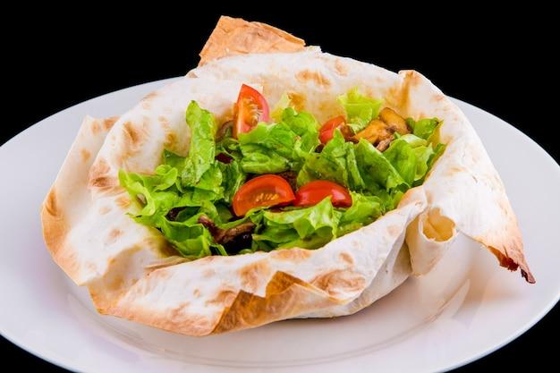 얇은 피타 빵에 따뜻한 샐러드: 쇠고기, 버섯, 방울 토마토, 디종 머스타드, 코냑. 검은 배경에 고립