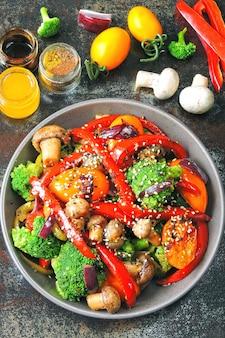 Теплый салат с брокколи, грибами и красной паприкой. веганские чаши с теплыми овощами на стильном фоне потертый. здоровая пища. фитнес-ланч с грибами и овощами.