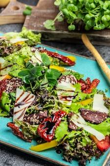 子牛のグリル、レタス、パルメザンチーズ、サンドライトマトの温かいサラダ。健康的な脂肪、減量のためのきれいな食事。肉サラダ。食品レシピの背景。閉じる。