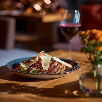 レストランのテーブルに子牛のグリル、トマト、ナス、赤ワインのグラスを添えた温かいサラダ