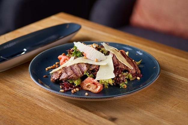 Теплый салат с телятиной на гриле, помидорами, баклажанами на столе в ресторане
